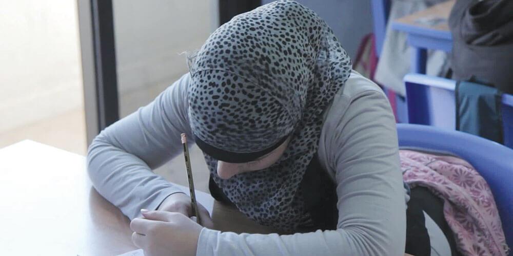 Criança refugiada síria estuda em um dos centros de influência. Crédito: Chanmin Chung