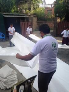 Funcionários da ADRA Internacional e da ADRA Nepal preparam lonas que serão distribuídas para abrigar vítimas do terremoto. Foto: ADRA Nepal