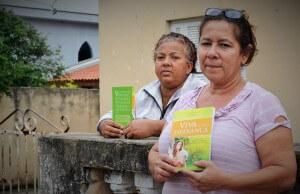 Roseli Pedroso (no primeiro plano) viu o livro pela TV Novo Tempo e ficou surpresa ao receber um exemplar através dos voluntários que realizaram a campanha na cidade onde mora. Foto: Márcio Tonetti