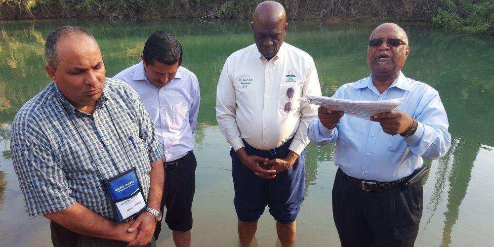 Líderes da igreja oram às margens do Rio Jordão