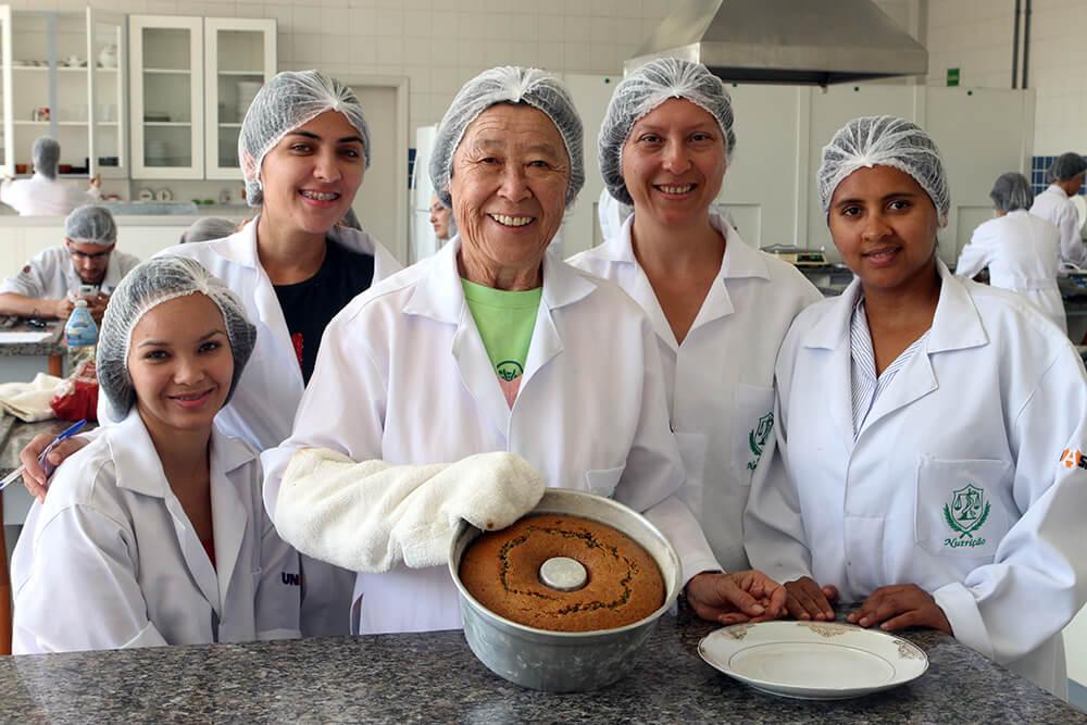 Acompanhada de colegas de classe no curso de Nutrição, dona Seetuko (ao centro) participa de uma aula de cozinha experimental no laboratório de técnicas dietéticas do Unasp, campus São Paulo. Créditos da imagem: Murilo Pereira